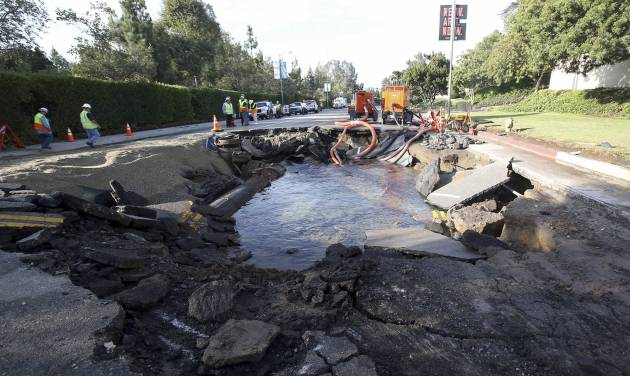 The site of a water main break is shown near UCLA Wednesday July 30, 2014, in Los Angeles. A ruptured 93-year-old water main on Tuesday left the UCLA campus awash in 8 million gallons of water in the middle of California's worst drought in decades, stranding people in parking garages and flooding the school's storied basketball court less than two years after a major renovation. (AP Photo/Nick Ut)