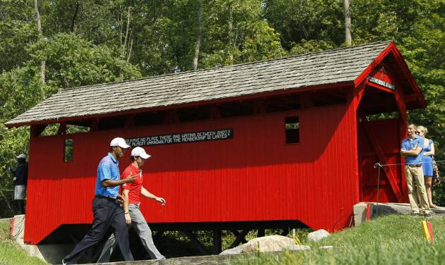 Tiger Woods, left, and Rory McIlroy, of Northern Ireland, walk past the covered bridge at the sixth hole during the first round of the BMW Championship PGA golf tournament at Crooked Stick Golf Club in Carmel, Ind., Thursday, Sept. 6, 2012. (AP Photo/Charles Rex Arbogast)