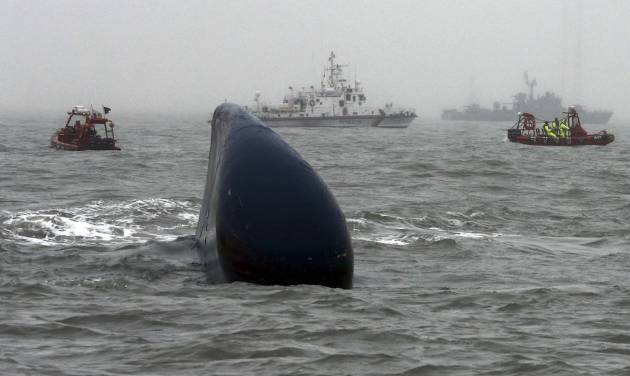 """FILE - In this April 18, 2014 file photo, South Korean Coast Guard officers search missing passengers aboard the ferry Sewol, center, in the water off the southern coast near Jindo, South Korea. The South Korean government is scrambling to fix what Prime Minister Park Geun-hye calls the """"deep-rooted evils"""" that contributed to last month's ferry sinking, which left more than 300 people dead or missing. As investigators probe cozy links between the shipping industry and its regulators, Seoul has promised new monitoring and regulations for domestic passenger ships, which are not governed by international rules. (AP Photo/Yonhap, File) KOREA OUT"""