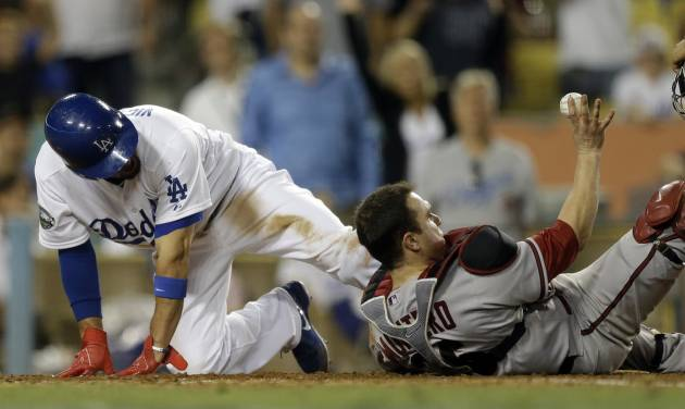 Arizona Diamondbacks catcher Miguel Montero, right, shows the umpire the ball after forcing Los Angeles Dodgers' Shane Victorino out at the plate during eighth inning of a baseball in Los Angeles, Saturday, Sept. 1, 2012. (AP Photo/Chris Carlson)