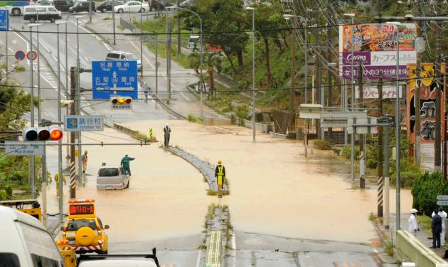 A road is submerged by an overflowed river following a typhoon in Yomitan, Okinawa, Wednesday, July 9, 2014. A powerful storm slammed through the southwestern Japanese island of Okinawa, leaving at least 28 people injured and 63,000 homes without power before swerving toward the bigger island of Kyushu on Wednesday. (AP Photo/Ryukyu Shimpo via Kyodo News) JAPAN OUT, NO SALES, NO ARCHIVE, MANDATORY CREDIT