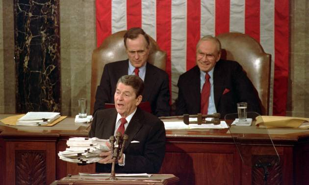 FILE - This Jan. 25, 1988 file photo shows President Ronald Reagan holding up 14-pound continuing resolution for the budget, part of a total package weighing 43-pounds, which the president said was two months late from Congress, during his State of the Union address on Capitol Hill in Washington on January 25, 1988.  Vice President George H.W. Bush, left, and House Speaker James Wright of Texas listen behind him. Last week's 1,582-page bill was really 12 bills wrapped into one, negotiated in the back rooms of the Capitol by a relative handful of people and presented to the House and Senate as an unamendable, take-it-or-leave-it proposition. (AP Photo/Bob Daugherty, File)