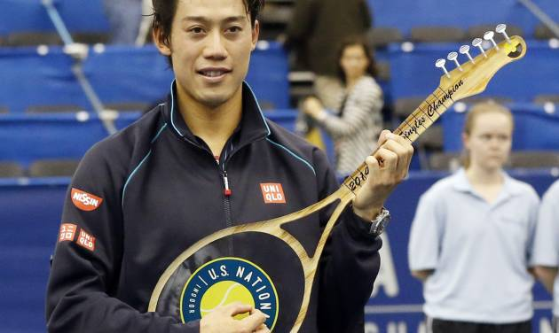 Kei Nishikori, of Japan, holds the winner's trophy after defeating Ivo Karlovic, of Croatia, 6-4, 7-6 (0) in the singles final at the U.S. National Indoor Tennis Championships, Sunday, Feb. 16, 2014, in Memphis, Tenn. The trophy is shaped like a guitar. (AP Photo/Rogelio V. Solis)