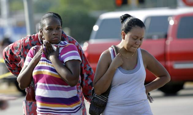 Parents,  Eunice Pacheco, right, and LaKesia Brent, left, wait for news about their children outside Spring High School Wednesday, Sept. 4, 2013, in Spring, Texas.  A 16-year-old boy has been airlifted from the school in suburban Houston with stab wounds suffered in an altercation at the campus. The Harris County Sheriff's Office says it responded about 7 a.m. Wednesday to Spring High School to a report of a stabbing. Spring is about 20 miles north of Houston.  (AP Photo/David J. Phillip)