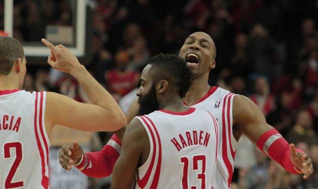Houston Rockets center Dwight Howard, right, celebrates with teammates James Harden (13) and Francisco Garcia, left, after scoring to defeat the Washington Wizards 113-112 at the end of an NBA basketball game in Houston, Wednesday, Feb. 12, 2014. (AP Photo/Richard Carson)