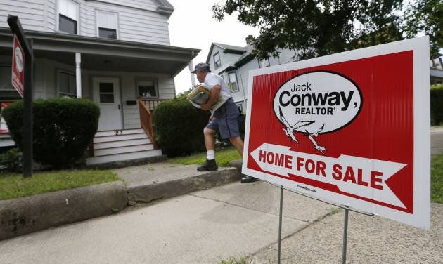 In this July 10, 2014 photo, a mailman delivers mail to a house for sale in Quincy, Mass. The National Association of Realtors reports on existing-home sales in June on Tuesday, July 22, 2014. (AP Photo/Michael Dwyer)
