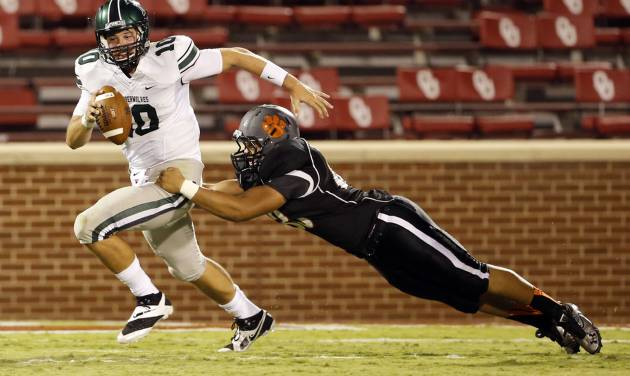 Norman's High's Cade Parker tackles Norman North's quarterback David Cornwell (10) for a loss in the second quarter at Gaylord Family-Oklahoma Memorial Stadium in Norman, Okla., on Thursday, Sept. 5, 2013. Photo by Steve Sisney, The Oklahoman