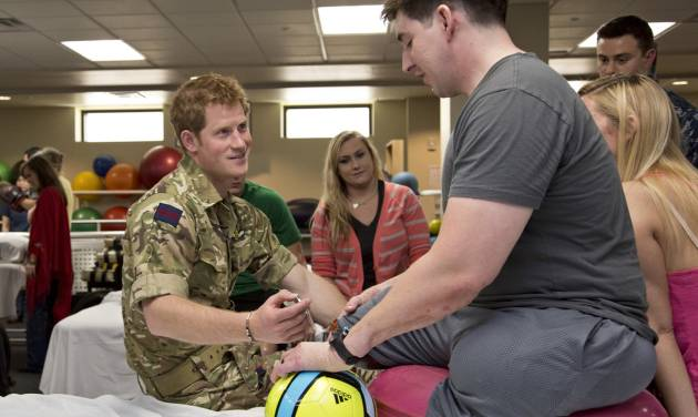 Wearing his British Army uniform, Britain's Prince Harry visits with wounded warriors undergoing physical therapy at the Military Advanced Training Center at Walter Reed National Military Medical Center in Bethesda, Md., just outside Washington, Friday, May 10, 2013. At right is Staff Sgt. Timothy Payne who lost his legs in an IED explosion in Afghanistan.  (AP Photo/J. Scott Applewhite, Pool)
