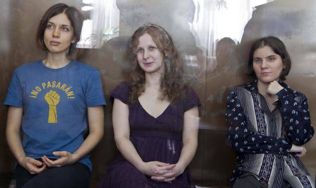 FILE In this Wednesday, Aug. 8, 2012 file photo feminist punk group Pussy Riot members, from left, Nadezhda Tolokonnikova, Maria Alekhina and Yekaterina Samutsevich sit in a glass cage at a court room in Moscow, Russia. Three members of Pussy Riot were jailed in March and charged with hooliganism motivated by religious hatred after their punk performance against President Putin in Moscow's main cathedral. Theyare awaiting the verdict on Friday, Aug. 17, 2012. (AP Photo/Misha Japaridze, file)