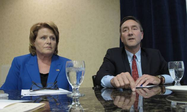 Democratic U.S. Senate candidate Heidi Heitkamp, left, listens to Republican opponent Rick Berg, right, speak at a North Dakota Chamber of Commerce forum on health care and energy at a hotel in Bismarck, N.D., on Thursday, Oct. 11, 2012. A recent poll put the two candidates in a dead heat three weeks before the election. A Berg victory is crucial to Republican hopes of gaining control of the U.S. Senate. (AP Photo/Dale Wetzel)