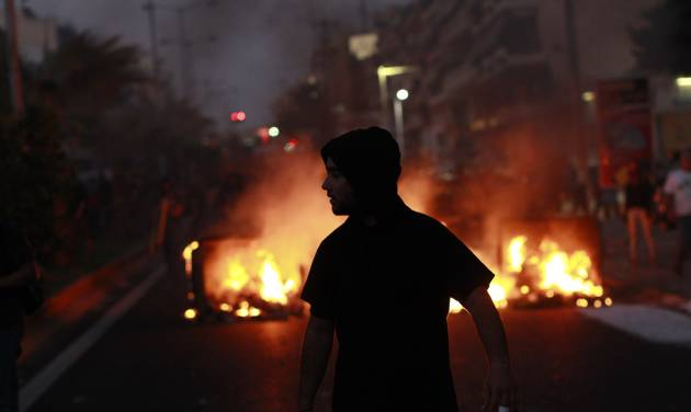 A protester walks in front of a burning barricade, during a protest after the stabbing of a 34 year old man in the suburb of Keratsini near Athens , Wednesday, Sept. 18 2013.  Violent clashes broke out Wednesday in several Greek cities after a member of the country's far-right Golden Dawn party was arrested in the fatal stabbing of a 34-year-old musician described as an anti-fascist activist. The stabbing drew condemnation from across Greece's political spectrum and from abroad. While the extremist Golden Dawn has been blamed for numerous violent attacks in the past, the overnight stabbing is the most serious violence directly attributed to a member so far. (AP Photo/Kostas Tsironis)
