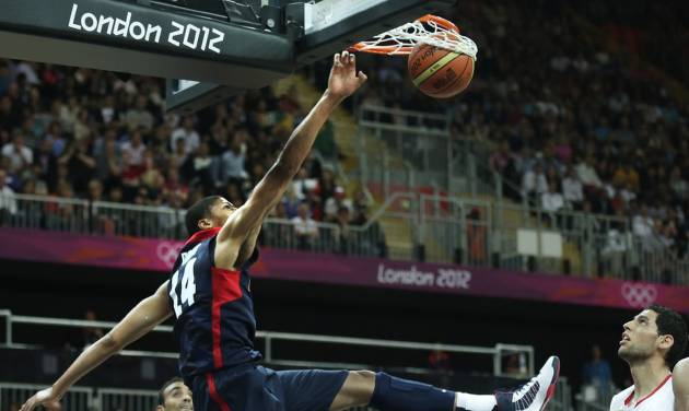 USA's Anthony Davis slams a dunk between Tunisian players during a men's basketball game at the 2012 Summer Olympics, Tuesday, July 31, 2012, in London. (AP Photo/Charles Krupa)