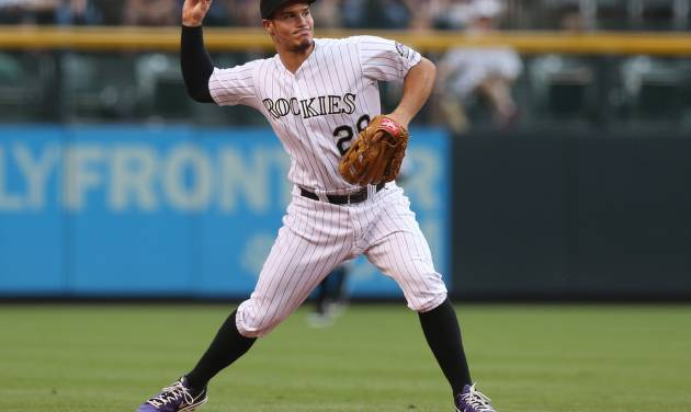 Colorado Rockies third baseman Nolan Arenado throws to first base to put out Pittsburgh Pirates' Andrew McCutchen in the first inning of a baseball game in Denver on Saturday, July 26, 2014. (AP Photo/David Zalubowski)