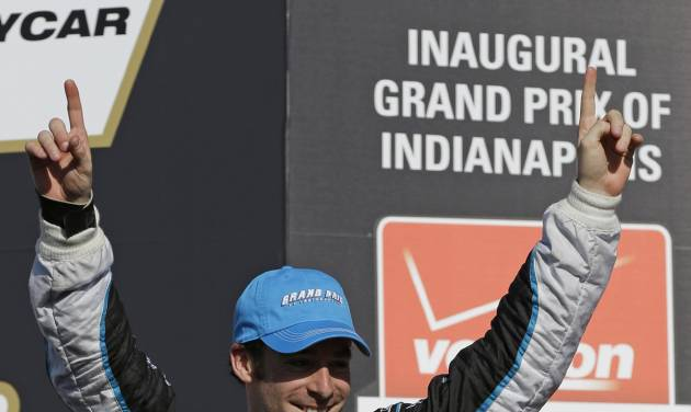 Simon Pagenaud, of France, celebrates as he walks to the podium after winning the inaugural Grand Prix of Indianapolis IndyCar auto race at the Indianapolis Motor Speedway in Indianapolis, Saturday, May 10, 2014. (AP Photo/Michael Conroy)