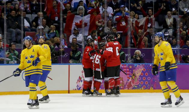 Team Sweden skates back to the bench as Canada celebrates a goal during the first period of the men's gold medal ice hockey game at the 2014 Winter Olympics, Sunday, Feb. 23, 2014, in Sochi, Russia. (AP Photo/Julio Cortez)