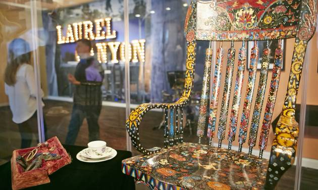 """In this Friday, May 9, 2014 photo, Grammy Museum Executive Director Bob Santelli, left, comments of The Mamas & the Papas singer Cass Elliot's chair, left, on display at the Grammy Museum exhibit """"California Dreamin': The Sounds of Laurel Canyon, 1965 - 1977,"""" in Los Angeles Friday, May 9, 2014. (AP Photo/Damian Dovarganes)"""