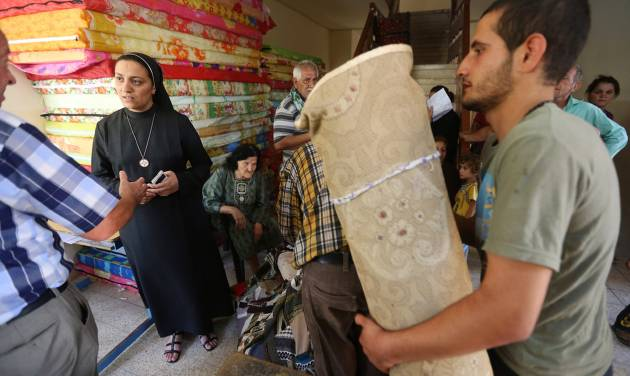 FILE - In this Friday, June 27, 2014, file photo, an Iraqi nun, second from left, speaks with a Christian man who fled with his family from the Christian villages near Mosul, Iraq, at a school that was turned into a shelter for displaced Christian families, in Ainkawa, a suburb of Irbil, Iraq. The Islamic State group gave Mosul's Christians until midday Saturday, July 19, 2014, to convert to Islam, pay a tax or face death. The vast majority of Christians fled. (AP Photo/Hussein Malla, File)
