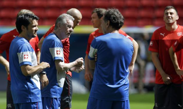 Switzerland's coach Ottmar Hitzfeld, second left, talks to staff members and players during an official training session the day before the group E World Cup soccer match between Switzerland and Ecuador at the Estadio Nacional in Brasilia, Brazil, Saturday, June 14, 2014.  (AP Photo/Michael Sohn)