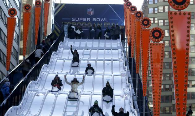 People make their way down the toboggan slide during Super Bowl Boulevard festivities Wednesday, Jan. 29, 2014, in New York. The Seattle Seahawks are scheduled to play the Denver Broncos in the NFL Super Bowl XLVIII football game on Sunday, Feb. 2, in East Rutherford, N.J. (AP Photo/Julio Cortez)