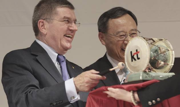 Thomas Bach, left, president of the IOC beats a Korean traditional drum as Hwang Chang-gyu, chairman of KT, smiles after the signing of a partnership between Pyeongchang's organizing committee and KT in Seoul, South Korea, Tuesday, July 1, 2014. Under their partnership, KT will provide high-speed Internet service throughout the competition using up-to-date technology and will help Pyeongchang host the most advanced Olympic Games in terms of information and communication technology. (AP Photo/Ahn Young-joon)