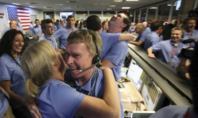 Telecom engineer Peter Llott, center, hugs a colleague to celebrate the successful landing of NASA's Mars Science Laboratory Curiosity rover inside the Spaceflight Operations Facilityat the Jet Propulsion Laboratory in Pasadena, Calif., Sunday, August 5, 2012. The Curiosity robot is equipped with a nuclear-powered lab capable of vaporizing rocks and ingesting soil, measuring habitability, and potentially paving the way for human exploration. (AP Photo/Brian van der Brug, Pool)