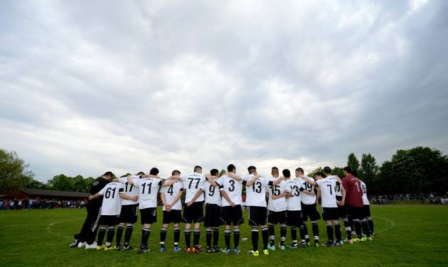 "In this picture taken Wednesday, April 30, 2014, the soccer team of 17-year old German exchange student Diren Dede SC Teutonia 1910 holds a minute of silence prior to a soccer match in Hamburg, northern Germany. The father of the student who was killed in the United States criticized the country's gun laws upon his arrival in Montana where his son was fatally shot. Celal Dede told the German news agency dpa Thursday that ""America cannot continue to play the cowboy."" (AP Photo/dpa, Daniel Reinhardt)"