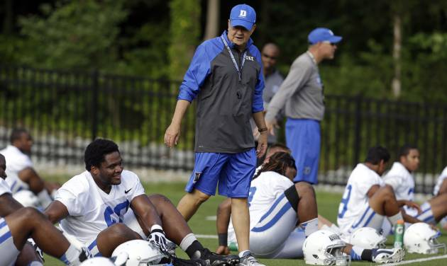 FILE - In this Monday, Aug. 5, 2013, file photo, Duke coach David Cutcliffe chats with players as they stretch during an NCAA college football practice in Durham, N.C. A growing number of college coaches are watching the social media behavior of student athletes, including Cutcliffe. (AP Photo/Gerry Broome, File)