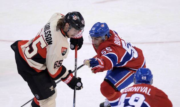 Ottawa Senators defenceman Erik Karlsson attempts to get the puck past Montreal Canadiens defenseman Francis Bouillon and forward Michael Bournival during second period NHL hockey action in Ottawa on Friday, April 4, 2014.  (AP Photo/The Canadian Press, Sean Kilpatrick)