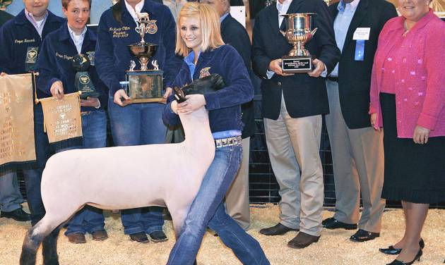 Charlcey Vinyard poses with her grand champion lamb during the Oklahoma Youth Expo Sale of Champions at State Fair Park. The lamb sold for $22,000 to Touchstone Energy. Behind Vinyard are Cooper Newcomb, Carson Vinyard, McKenzie Clifton, Ted Farris, Bob Newcomb, David Henry, Kevin Cates and Lt.  Gov. Jari Askins. Photo BY JOHN CLANTON, THE OKLAHOMAN