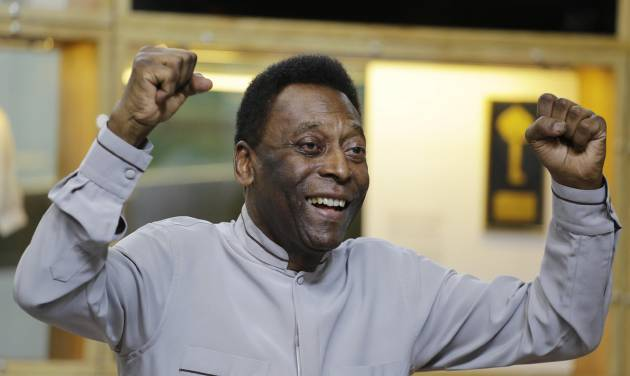 Soccer great Pele pose for photos during the inauguration of the Pele Museum showing his history as a player in Santos, Brazil, Sunday, June 15, 2014. The Pele Museum exhibits his personal collection, pictures, films, trophies and printed material about his history as a soccer player and personality. (AP Photo/Nelson Antoine)