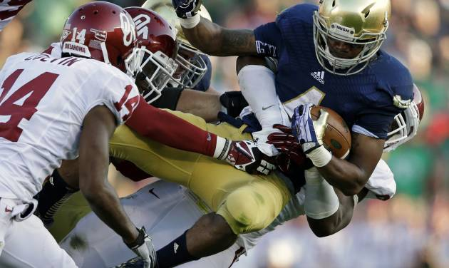 Notre Dame's George Atkinson III (4) is tackled by Oklahoma's Geneo Grissom, behind, during the second half of an NCAA college football game on Saturday, Sept. 28, 2013, in South Bend, Ind. Oklahoma defeated Notre Dame 35-21. (AP Photo/Darron Cummings)