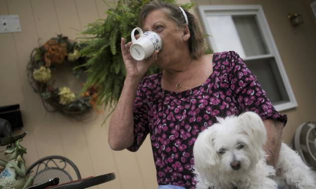 CORRECTS TYPE OF MENINGITIS TO FUNGAL INSTEAD OF BACTERIAL - Patsy Bivins, 68 of Sturgis, Ky., drinks coffee while sitting on her porch with her dog Little Britches at her apartment in Sturgis, Ky., Friday, October 5, 2012. Bivins was injected with steroids at St. Mary Sugricare in Evansville, Ind., who notified her of possibly being infected with fungal Meningitis. (AP Photo/Stephen Lance Dennee)