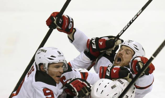 New Jersey Devils' Zach Parise (9), Alexei Poonikarovsky (12), Marek Zidlicky (2) and David Clarkson, top right, mob Adam Henrique, obsucred, after he scored during the second overtime against the Florida Panthers in Game 7 in a first-round NHL Stanley Cup playoff hockey series in Sunrise, Fla., Wednesday, April 26, 2012. The Devils won 3-2. (AP Photo/J Pat Carter)