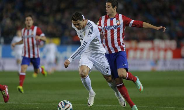 Atletico's Javi Manquillo, bottom, commits a foul on Real's Cristiano Ronaldo, front, during a semi final, 2nd leg, Copa del Rey soccer match between Atletico de Madrid and Real Madrid at the Vicente Calderon stadium in Madrid, Spain, Tuesday, Feb. 11, 2014. (AP Photo/Andres Kudacki)