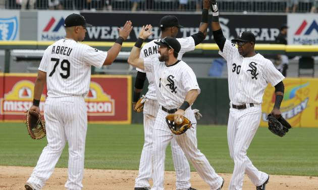 Chicago White Sox players, from left, Jose Abreu, Alexei Ramirez, Adam Eaton, and Alejandro De Aza celebrate their 7-6 win over the San Francisco Giants in an interleague baseball game Wednesday, June 18, 2014, in Chicago. (AP Photo/Charles Rex Arbogast)