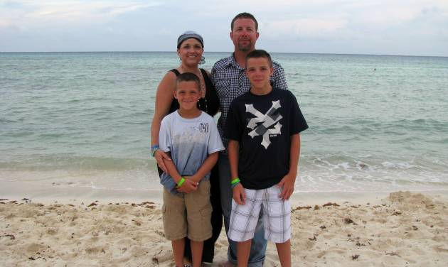 "In this August 2011 photo provided by Arrica Wallace, Wallace poses with her husband, Matthew, and sons Marccus and Mason in Mexico during a vacation, two weeks after her first round of chemotherapy. Arrica Wallace was 35 when her cervical cancer was discovered in 2011. It spread widely, with one tumor so large that it blocked half of her windpipe. The strongest chemotherapy and radiation failed to help, and doctors gave her less than a year to live. But her doctor heard about an immune therapy trial at the Cancer Institute and got her enrolled. ""It's been 22 months since treatment and 17 months of completely clean scans"" that show no sign of cancer, Arrica Wallace said. (AP Photo/Courtesy Arrica Wallace)"