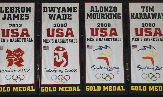 A banner commemorating Miami Heat forward LeBron James' participation on the gold-medal winning U.S. men's basketball team at this summer's London Olympics, far left, was unveiled during a ceremony before the start of an NBA basketball game against the Denver Nuggets, Saturday, Nov. 3, 2012 in Miami. His banner sways next to those honoring previous Heat players who were gold-medal winners: Dwyane Wade (2008), Alonzo Mourning (2000) and Tim Hardaway (2000). (AP Photo/Wilfredo Lee)