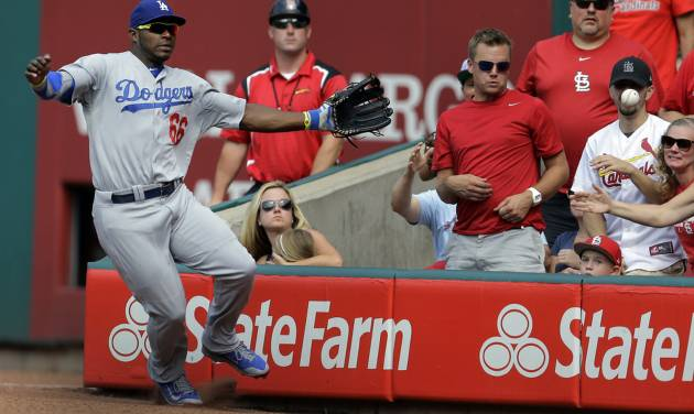 Los Angeles Dodgers right fielder Yasiel Puig cannot reach a foul ball hit by St. Louis Cardinals' Jhonny Peralta during the third inning of a baseball game Saturday, July 19, 2014, in St. Louis. (AP Photo/Jeff Roberson)