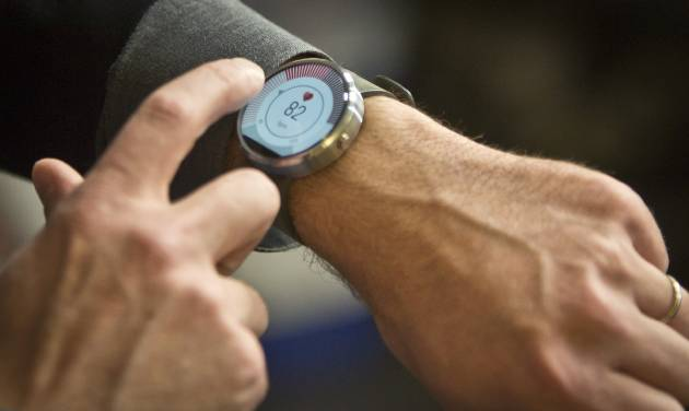 Steve Sinclair, Motorola's vice president of product management, demonstrates the new Moto 360 circular smartwatch, the company's first, during an interview, Wednesday Aug. 27, 2014 in New York.  (AP Photo/Bebeto Matthews)