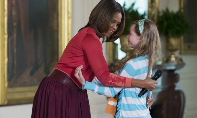 "First lady Michelle Obama hugs Charlotte Bell, 10, after she handed Mrs. Obama her dad's resume during the White House's annual ""Take Our Daughters and Sons to Work Day,"" Thursday, April 24, 2014, in the East Room of the White House in Washington. The girl in the front row at Thursday's event told the first lady that her dad had been out of work for three years. Then the girl popped up to hand Mrs. Obama her dad's resume saying ""My dad's been out of a job for three years and I wanted to give you his resume."" (AP Photo/ Evan Vucci)"