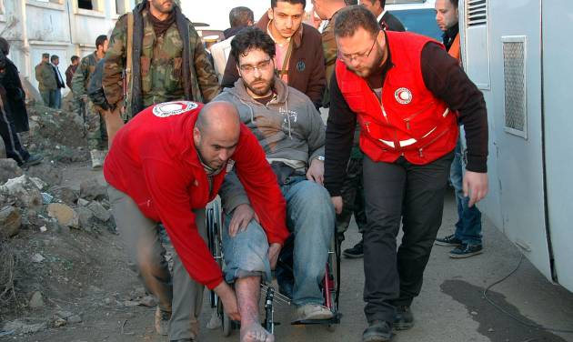 In this photo taken on Sunday Feb. 9, 2014, and released by the Syrian official news agency SANA, Syrian Arab Red Crescent members in red uniforms help evacuate an injured man on a bus out of the battleground city of Homs, Syria. A Syrian Red Crescent official says around 300 more people were evacuated Monday from besieged rebel-held neighborhoods of Syria's third-largest city, Homs. (AP Photo/SANA)