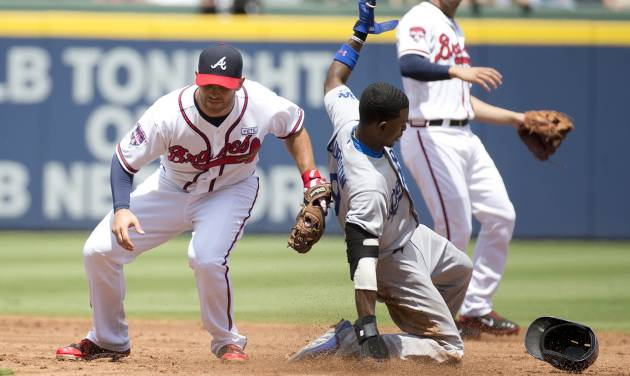 Los Angeles Dodgers' Dee Gordon (9) steals second base as Atlanta Braves second baseman Tommy La Stella (7) applies the late tag in the third inning of a baseball game Thursday, Aug. 14, 2014, in Atlanta. (AP Photo/John Bazemore)