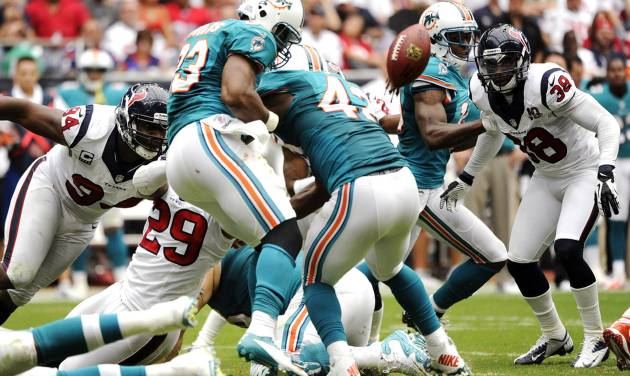 Miami Dolphins running back Daniel Thomas (33) fumbles the ball as he is hit by Houston Texans strong safety Glover Quin (29) in the second quarter of an NFL football game, Sunday, Sept. 9, 2012, in Houston. The Texans recovered the fumble. (AP Photo/Dave Einsel)