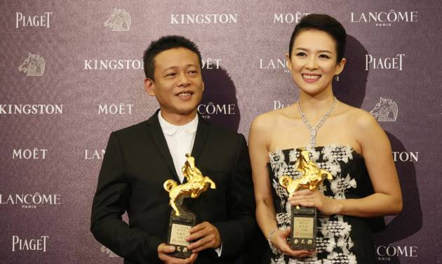 """Best Leading Actor Lee Kang Sheng, left, and actress Zhang Ziyi hold their awards for their films """" Stray Dogs """" and """" The Grandmaster """"at the 50th Golden Horse Awards in Taipei, Taiwan, Saturday, Nov. 23, 2013. The Golden Horse Awards is the Chinese-language film industry's biggest annual events. (AP Photo/Wally Santana)"""