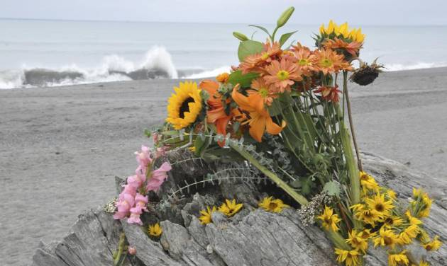 Flowers are rest on a large drift log yards from the breaking surf of the Big Lagoon beach near Trinidad, Calif. on Monday, Nov. 26, 2012. A family that tried to rescue their dog from powerful surf at the beach in Northern California were swept out to sea, leaving the parents dead and their 16-year-old son missing, authorities said. (AP Photo/The Times-Standard, Jose Quezada)