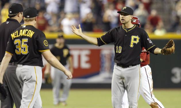 Pittsburgh Pirates' Jordy Mercer (10) and Mark Melancon (35) argue with umpire Lance Barrett, left, after Arizona Diamondbacks runner Nick Ahmed deflected the attempted throw by Mercer on a double play attempt allowing the winning run to score during the 10th inning of a baseball game on Sunday, Aug. 3, 2014, in Phoenix. The Diamondbacks defeated the Pirates 3-2. (AP Photo/Ross D. Franklin)