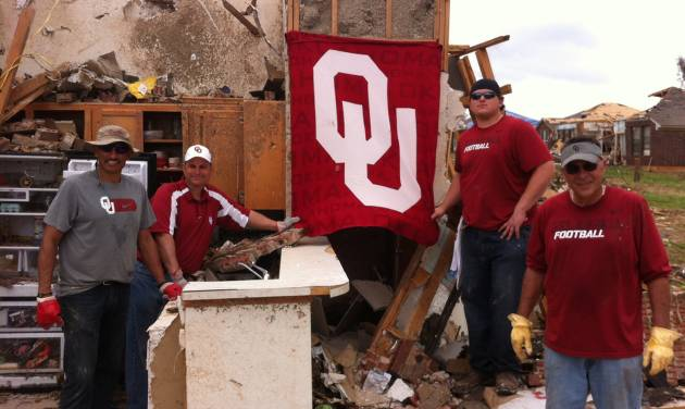 Oklahoma assistant Jay Norvell, athletic director Joe Castiglione, football player Bronson Irwin and assistant Tim Kish helped out in the Heatherwood neighborhood of Moore on Saturday. Among the things found in the rubble was an OU flag. PHOTO PROVIDED BY OU SPORTS INFORMATION