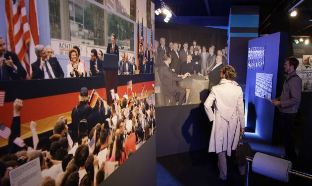 A man and a woman look at photos of US President Ronald Reagan delivering a speech at the Brandenburg Gate and then German Chancellor Helmut Kohl negotiating the German reunification with Soviet leader Michail Gorbachev inside the new cold war museum 'Black Box' at the Checkpoint Charlie in Berlin, Germany, Thursday, Sept. 20, 2012. (AP Photo/Michael Sohn)