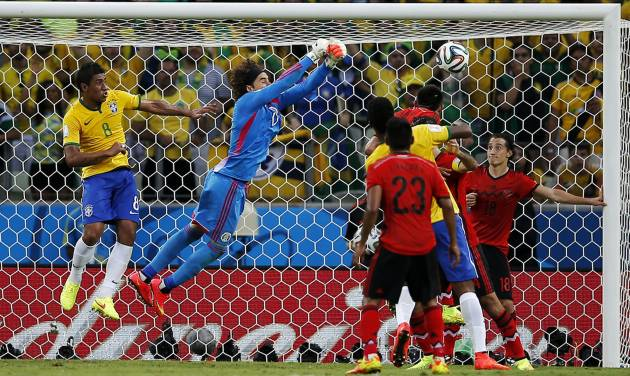 Brazil's Paulinho (8) watches as Mexico's goalkeeper Guillermo Ochoa punches the ball clear of the goal during the group A World Cup soccer match between Brazil and Mexico at the Arena Castelao in Fortaleza, Brazil, Tuesday, June 17, 2014.  (AP Photo/Eduardo Verdugo)