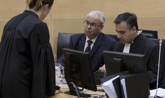 Representatives of Libya, Ahmad Sadeq Al Gehani, center, and Payam Akhavan, right, speak to an International Criminal Court staff member before a public hearing on Libya's challenge to the admissibility of the case against Seif Al-Islam Gaddafi in The Hague, Netherlands, Tuesday Oct. 9 2012. The International Criminal Court is holding a two-day hearing into where the eldest son of former Libyan dictator Moammar Gadhafi should be put on trial. Seif al-Islam Gadhafi is charged by the international court with crimes against humanity for his alleged involvement in the deadly crackdown on dissent against his father's rule. However Libyan authorities say they want to prosecute him at home, where he is being held. (AP Photo/Michael Kooren, POOL)